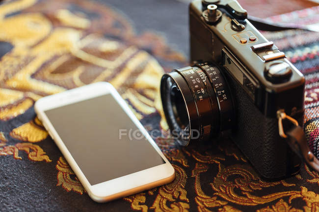 Closeup of vintage camera and smartphone on decorative table — Stock Photo