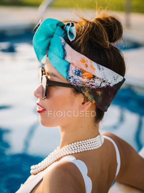 Close-up of young rich chinese woman relaxing at swimming pool at luxurious resort — Stock Photo