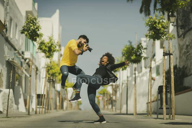 Bello ragazzo barbuto con macchina fotografica per scattare foto di donna urlando e piegandosi di nuovo sulla strada della città — Foto stock