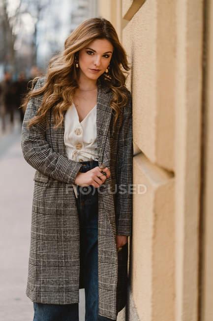 Portrait de la jeune femme élégante penchée sur le mur sur la rue — Photo de stock