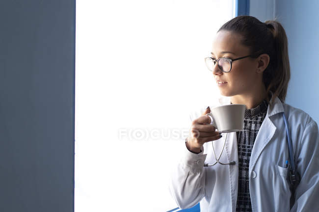 Young female doctor in uniform drinking from cup in room — Stock Photo