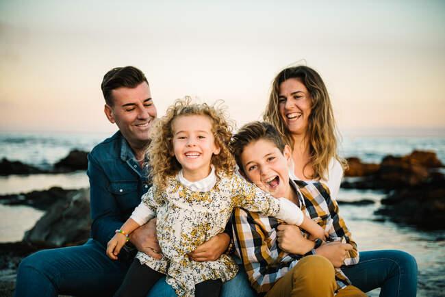 Мужчина средних лет женщина с детьми на берегу моря улыбается и обнимает друг друга — стоковое фото