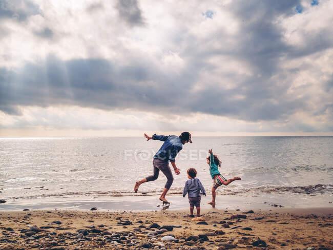 Padre casuale giocare con i suoi figli in riva al mare — Foto stock
