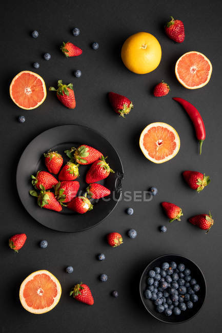 Various fresh fruits and berries scattered on black background — Stock Photo