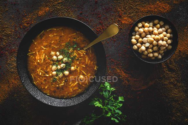 Soupe traditionnelle Harira pour Ramadan dans un bol noir sur une table sombre avec coriandre fraîche et pois chiches — Photo de stock