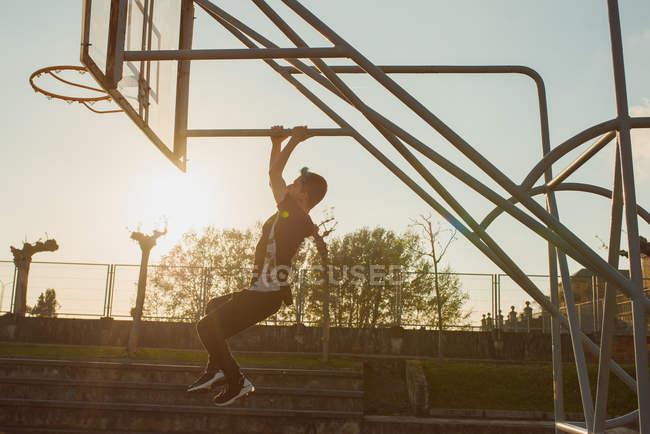 Невпізнанний підліток висить позаду баскетбольне кільце — стокове фото
