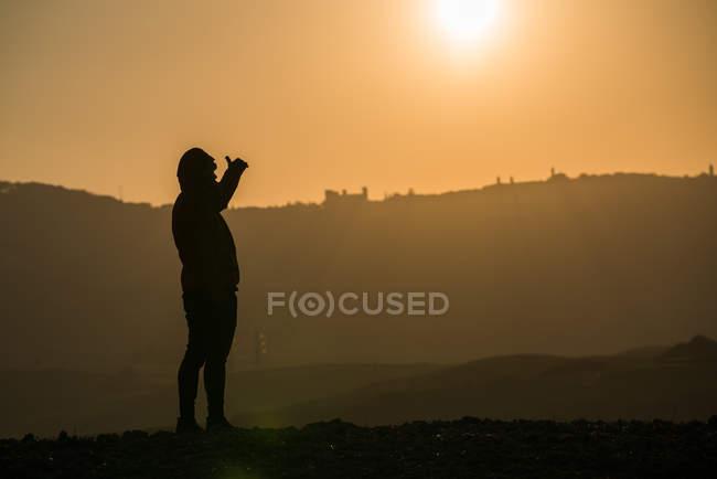 Silhouette de la personne debout sur le terrain dans le dos lumineux éclairé du ciel couchant, Italie — Photo de stock