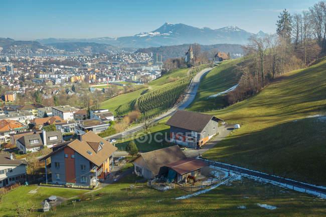 Живописный пейзаж маленького городка и дороги в долине зеленых гор, Швейцария — стоковое фото