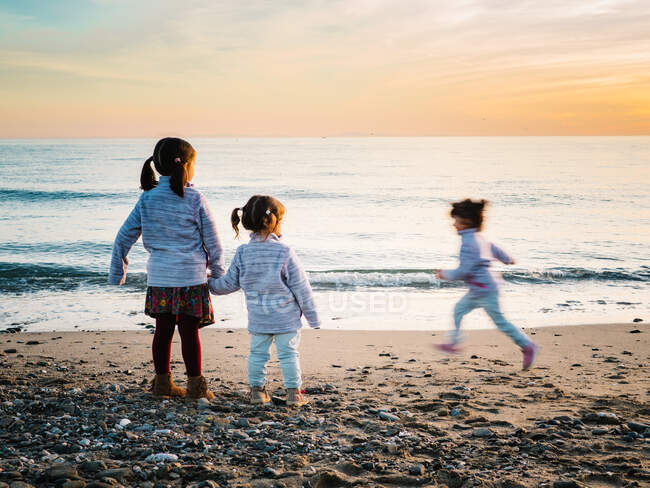 Small girls holding hands while other sister run at the beach on a winter day — Stock Photo