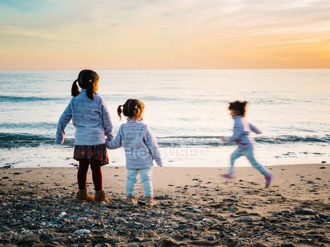 Маленькі дівчата тримаються за руки, а інша сестра біжить на пляжі в зимовий день. — стокове фото