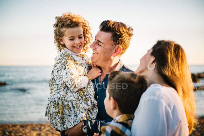 Middle aged man an woman with children at sea shore smiling and hugging each other — Stock Photo