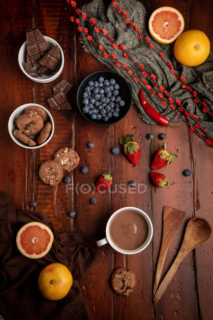 Fresh hot beverage and various tasty breakfast food placed on lumber tabletop in morning — Stock Photo