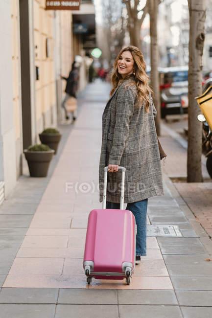 Приваблива жінка в модному пальто потягнувши рожевий чемодан і посміхаючись під час ходьби по міській вулиці і дивлячись на камеру — стокове фото