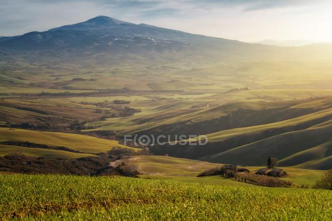 Величественный пейзаж зеленой долины с полями и горным хребтом в Тоскане, Италия — стоковое фото