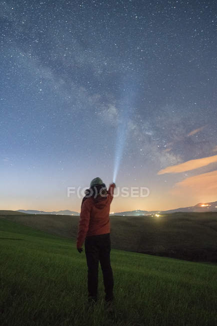 Back view of person standing in green highlands and glowing with torch in starry sky, Tuscany, Italy — Stock Photo
