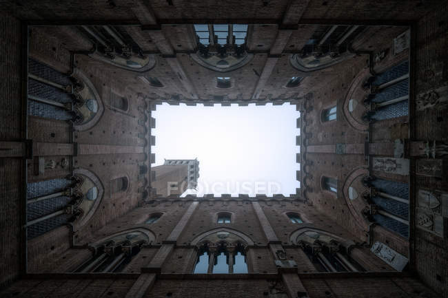 From below perspective view of masonry aged tower from courtyard, Tuscany, Italy — Stock Photo