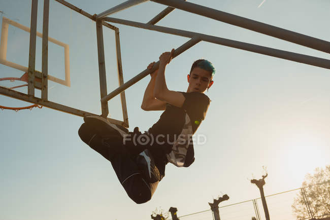 Підліток висить позаду баскетбольне кільце в сонячний день — стокове фото