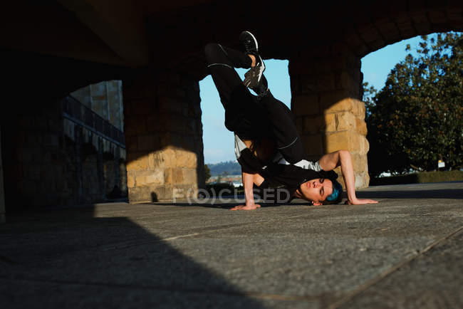 Teenager break dancing on street in sunlight — Stock Photo