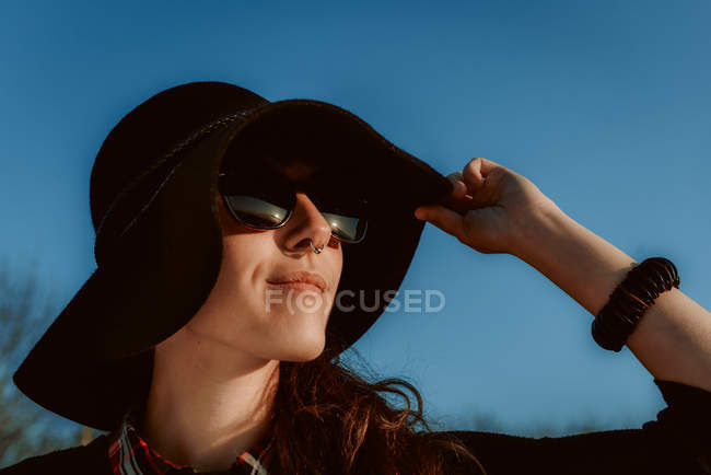 Happy woman wearing trendy sunglasses with black hat in sunlight — Stock Photo
