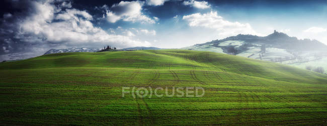View of beautiful endless green fields in bright sunlight under cloudy sky, Italy — Stock Photo