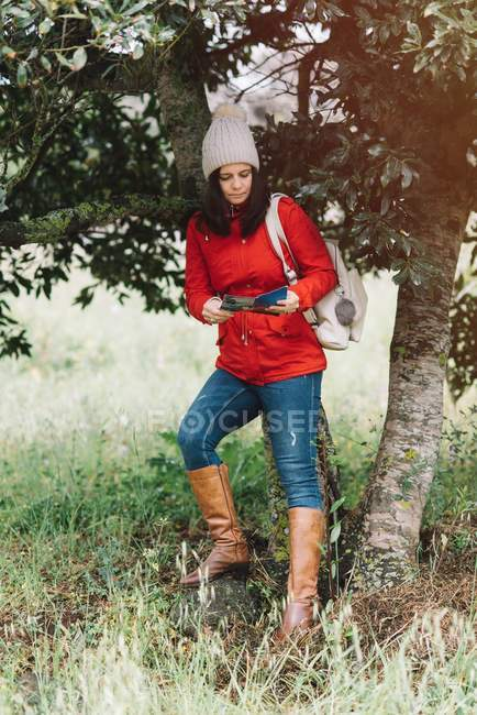 Pretty woman in warm clothes reading a guide booklet near tree in nature — Stock Photo