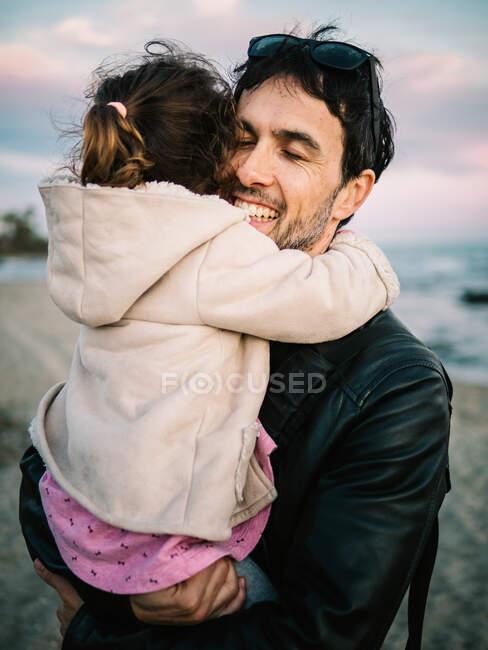 Linda escena de papá sosteniendo y abrazando a su hija pequeña en la playa en invierno - foto de stock