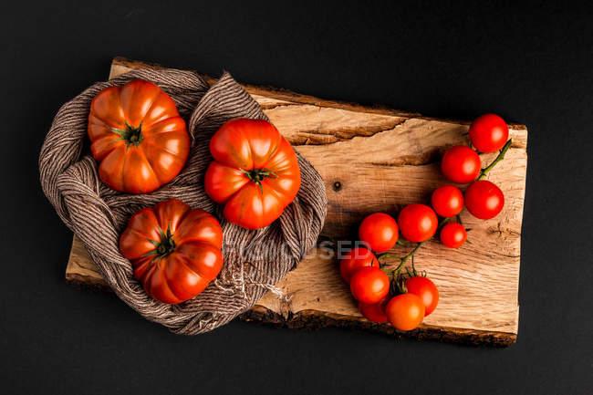 Tomates frescos maduros y servilleta de tela sobre madera sobre fondo negro - foto de stock