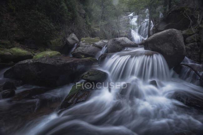 Пейзаж красивого водопада течет в условиях длительного воздействия на тяжелые валуны в диких лесах — стоковое фото