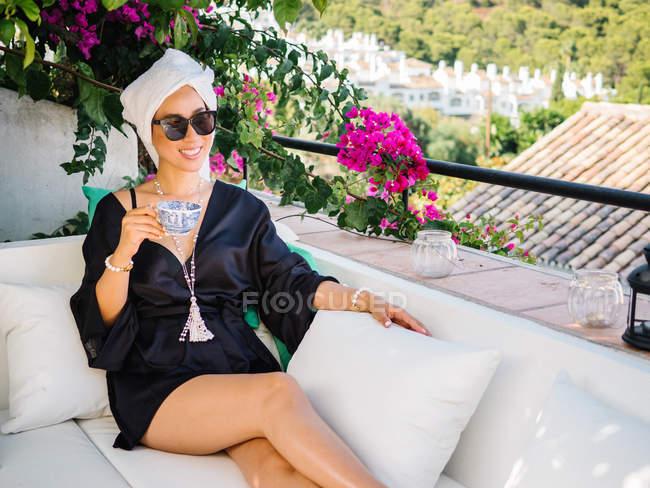 Chinoise jeune femme riche en satin noir robe de chambre et serviette dans la tête reposant sur un balcon bénéficiant de belles vues sur un matin ensoleillé et lumineux — Photo de stock