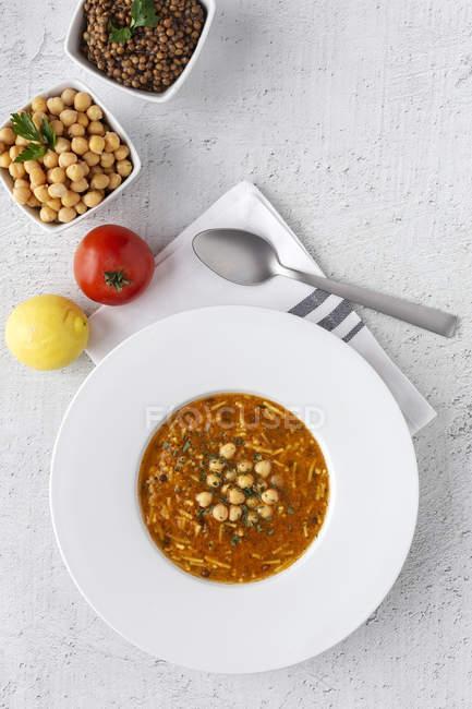 Soupe traditionnelle Harira pour Ramadan dans une assiette sur une table blanche avec des ingrédients — Photo de stock