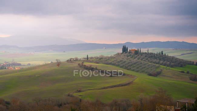 Великолепный пейзаж зеленых валунов с полями и горными хребтами под облачным закатным небом в Тоскане, Италия — стоковое фото