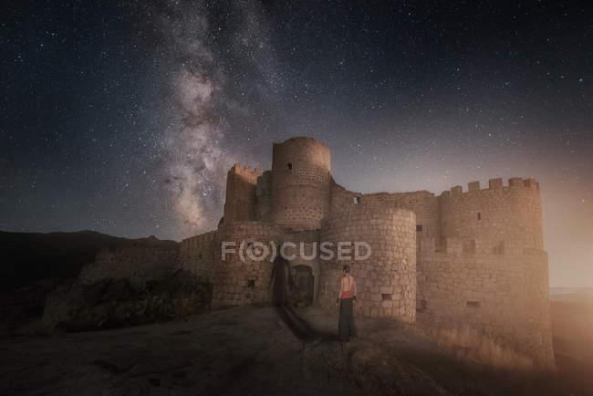 Силуэт человека, стоящего рядом с таинственной разрушенной древней крепостью на ночном звездном фоне — стоковое фото