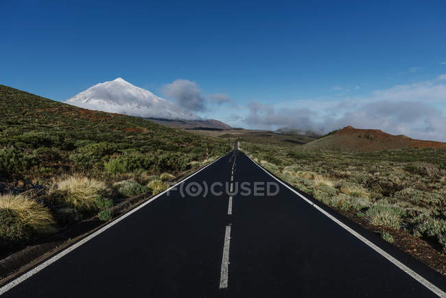 Asphalt countryside road through grassy terrain near snowy mountain peak on sunny day on Canary Islands, Spain — Stock Photo