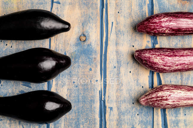 Set of fresh ripe purple and black eggplants on weathered wooden tabletop — Stock Photo