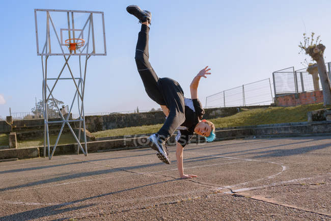 Teenager break dancing on sports ground in sunny day — Stock Photo
