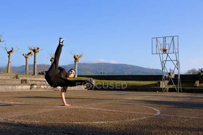 Teenager break dancing on sports ground — Stock Photo
