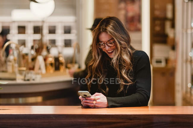 Cheerful female using smartphone in cafe — Stock Photo