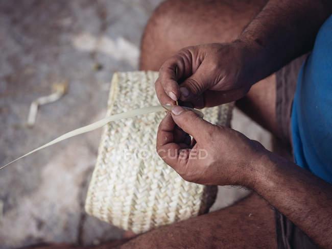Mãos fechadas do artesão anônimo tecendo fibras secas de folhas de palma enquanto trabalhava na oficina — Fotografia de Stock