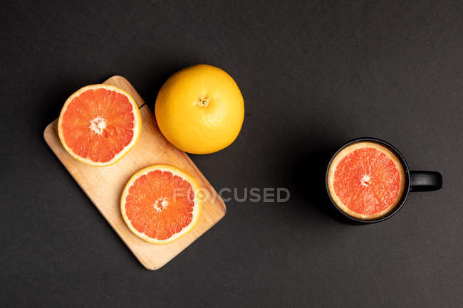 Sliced and whole grapefruits on black background near wooden board and mug — Foto stock