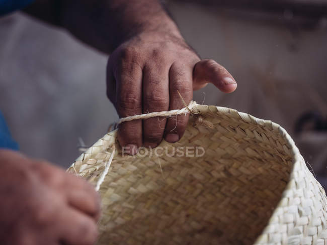 Руки анонимного ремесленника плетут прекрасную корзину из плетеного сушеного пальмового волокна — стоковое фото