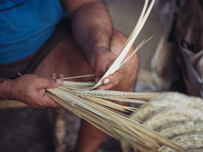 Руки анонимного ремесленника, готовящего сушеные пальмовые волокна для ткачества во время работы в мастерской — стоковое фото