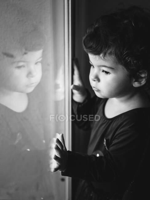 Чорно-білий портрет задумливого маленького хлопчика торкається вікна з віддзеркаленням себе на ньому. — стокове фото