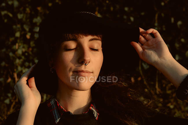 Young sensual brunette wearing black hat and accessories while posing in sunlight keeping eyes closed — Stock Photo