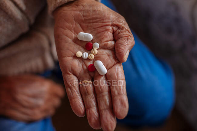 Detail of pills on the hand of an old man — Stock Photo
