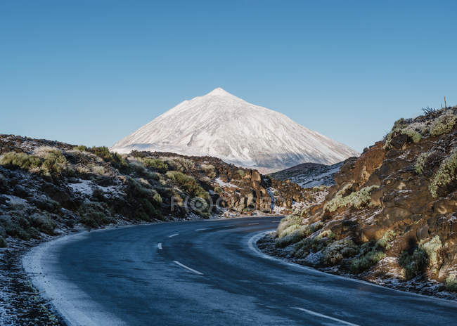 Asphalt countryside road through frozen grassy terrain near magnificent snowy mountain peak on sunny day on Canary Islands, Spain — Stock Photo