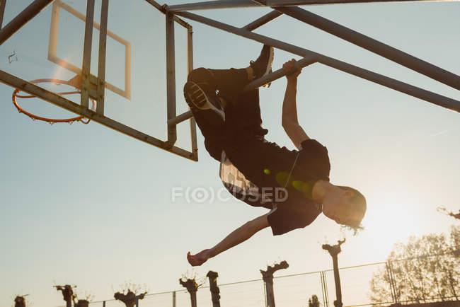 Невпізнанний підліток хлопчик в модному Екіпіровка висить догори дном на металеву структуру позаду баскетбольного обруча проти безхмарне небо з яскравим сонцем на спортивному грунті — стокове фото