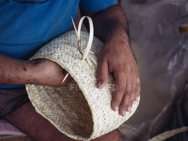 Hands of anonymous artisan holding lovely basket braided from dried palm fiber — Stock Photo