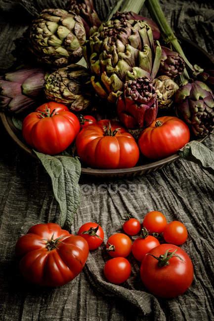 Conjunto de varias verduras frescas y servilleta de tela en mesa rústica - foto de stock