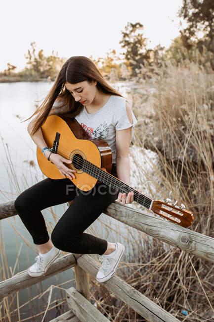 Досить молода жінка в повсякденному одязі грає на гітарі, сидячи на дерев'яному паркані біля спокійного озера в сонячний день. — стокове фото