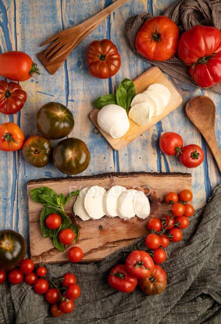Frische Tomaten und Mozzarella-Käse mit Basilikumblättern für Salat auf Holzbrett und Stoff — Stockfoto